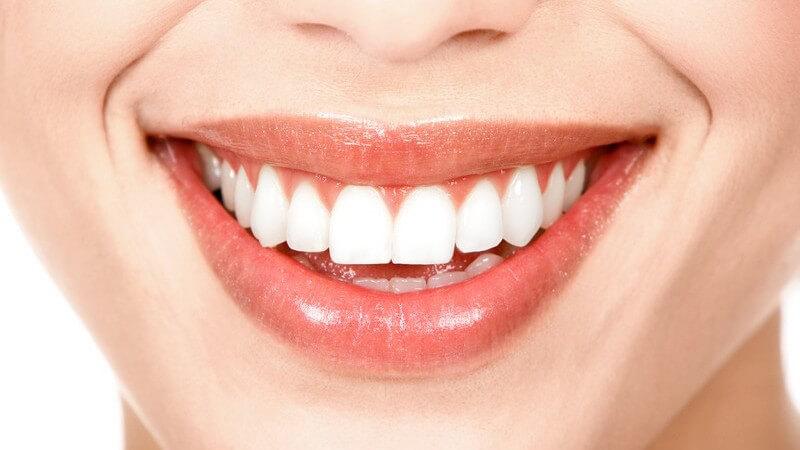 Nahaufnahme Unterer Teil des Gesichts einer Frau, lächelnder Mund, makellose, weiße Zähne, helle Haut, Hintergrund weiß