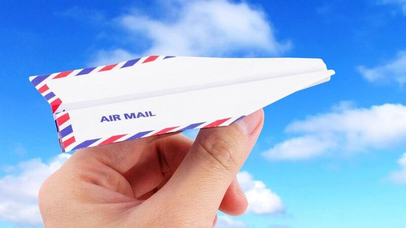 Hand hält Papier Flugzeug mit Aufschrift Air Mail unter blauem Himmel