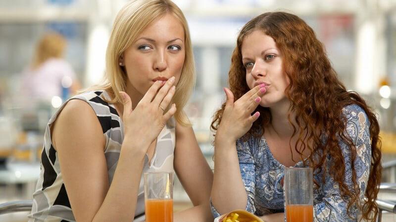 Zwei Freundinnen im Café lecken sich die Finger