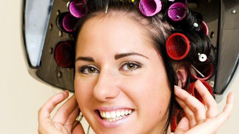 Junge Frau mit Lockenwicklern unter Trockenhaube beim Friseur