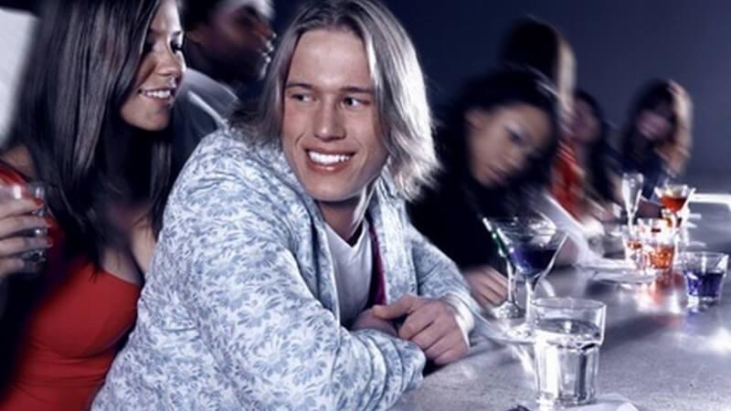 Junge braunhaarige Frau mit tiefem Dekolleté, Getränk und rotem Top steht hinter blondem Mann an der Theke