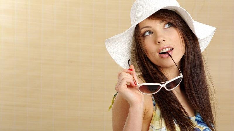 Junge braunhaarige Frau in Sommerbekleidung mit weißem Sonnenhut, sieht nach oben, Sonnenbrille keck im Mund