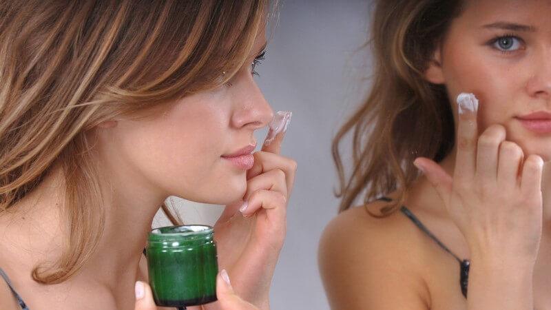 Junge Frau vor Spiegel trägt Gesichtscreme aus grünem Döschen auf