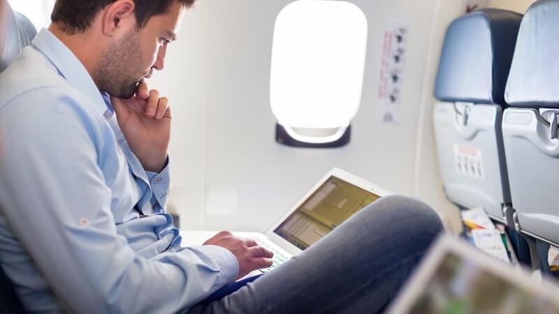 Geschäftsmann sitzt im Flugzeug und arbeitet am Laptop
