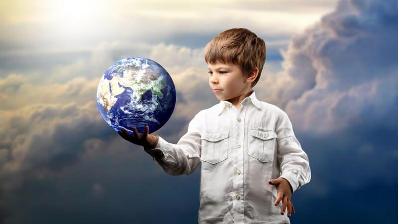 Kleiner Junge mit Globus in der Hand, dahinter Himmel über den Wolken