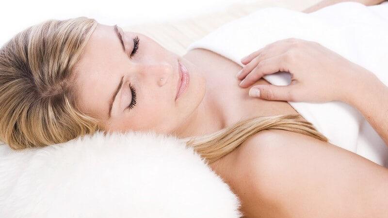 Blonde Frau schläft mit weißer Decke auf einem weißen Fellkissen