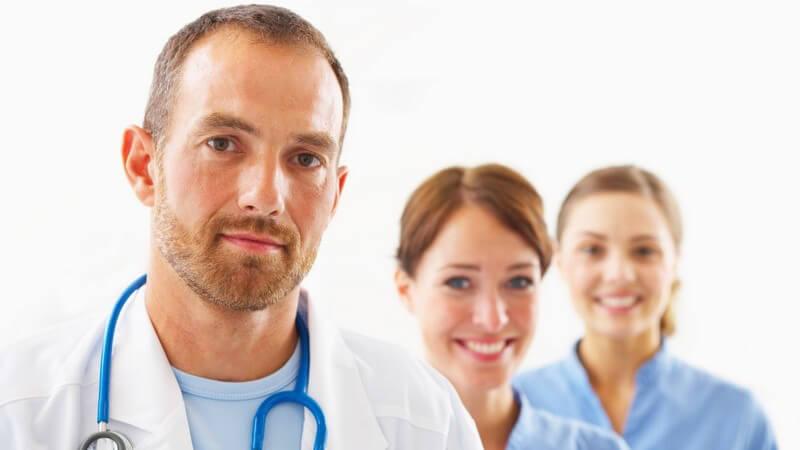 2 Ärztinnen, davor ein Arzt mit Stethoskop um den Hals