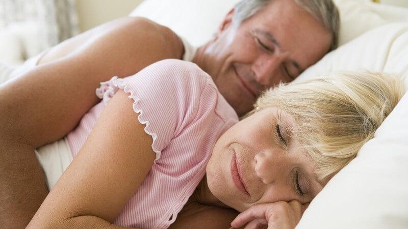Älteres Paar schläft im Bett, er hat von hinten Arm um sie gelegt