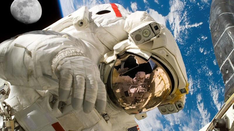 Astronaut im Weltall, im Hintergrund Erdkugel und Mond