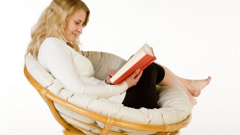Junge Frau im runden Sesselstuhl beim Lesen