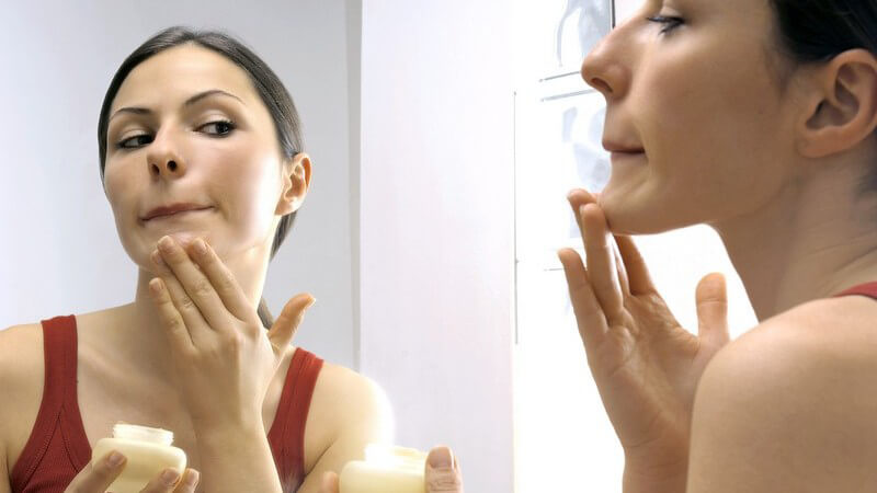 Junge Frau vor Spiegel trägt Gesichtscreme auf