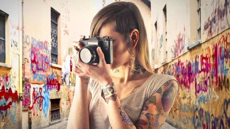Tätowierte Fotografin steht in einer Gasse mit vielen Graffitis und guckt durch die Linse ihrer Kamera