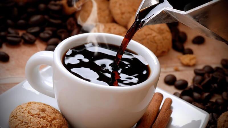 Frischer, dampfender Kaffee wird aus einer silbernen Kanne in die weiße Tasse gegossen, drumherum liegen Kekse