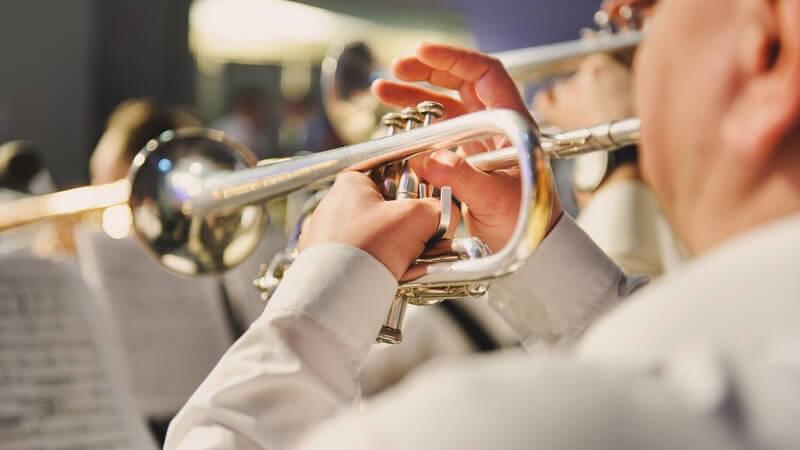 Mann spielt Trompete in einer Band oder einem Orchester