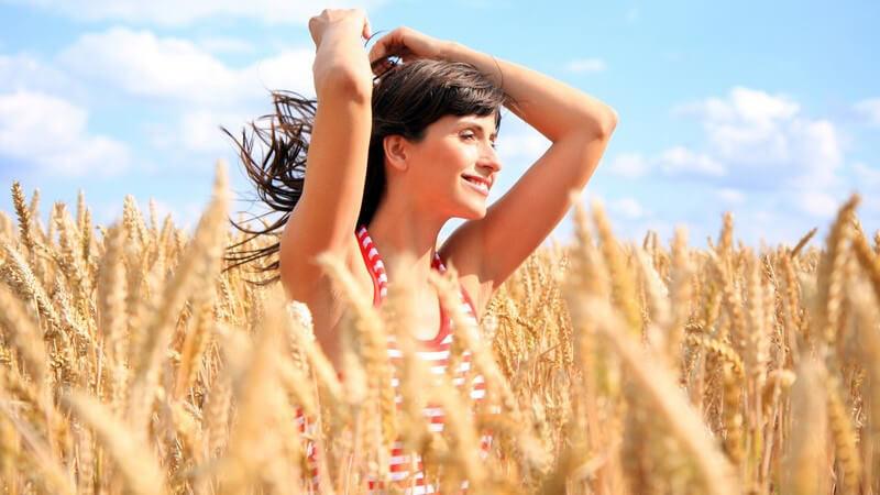 Dunkelhaarige Frau mit Neckholdertop, blauer Himmel und Sonne, in Getreidefeld mit Weizen und Ähren, Allergene