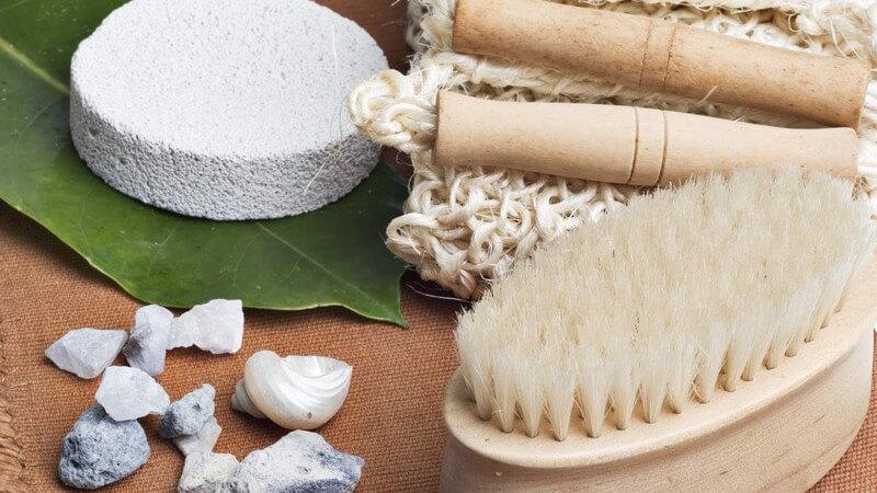 Bürste, Steine, Muscheln, Bimsstein auf einem Blatt und weiter Badeprodukte auf einem beigen Tuch