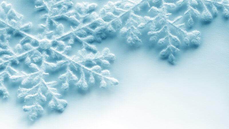 Grafik hellblaue Schneekristalle auf weißem Hintergrund