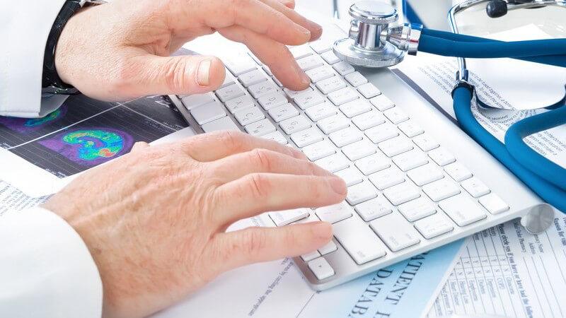 Arzt tippt etwas auf seiner Tastatur, blaues Stethoskop liegt daneben