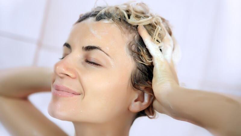 Lächelnde Frau wäscht sich unter der Dusche die Haare