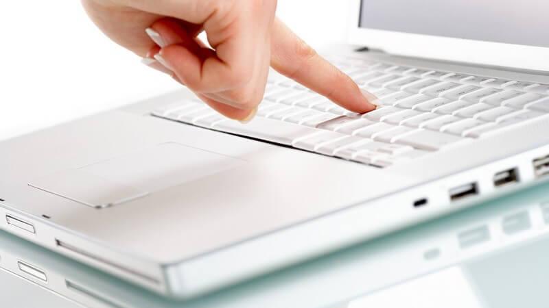 Nahaufnahme rechte Hand drückt auf Taste auf Computer Tastatur