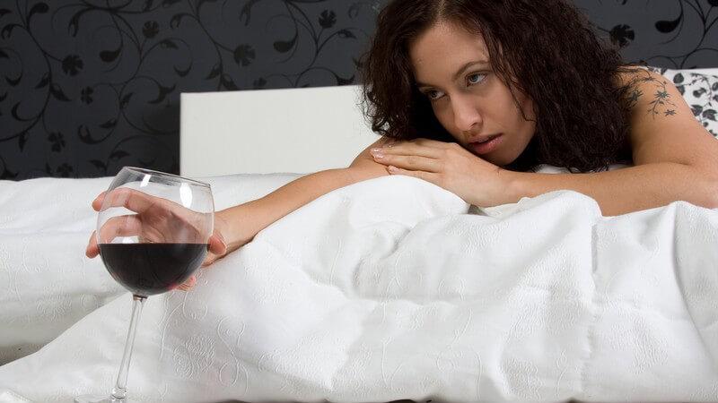 Junge Frau liegt allein im Bett und greift nach Glas Rotwein