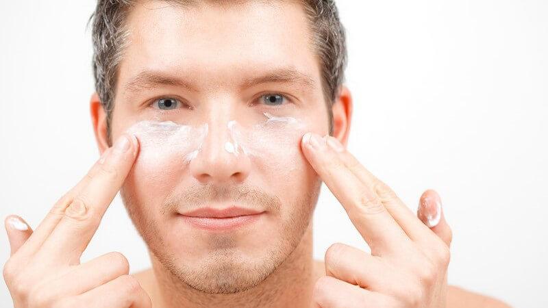 Mann trägt Creme auf Gesicht unter Augen auf