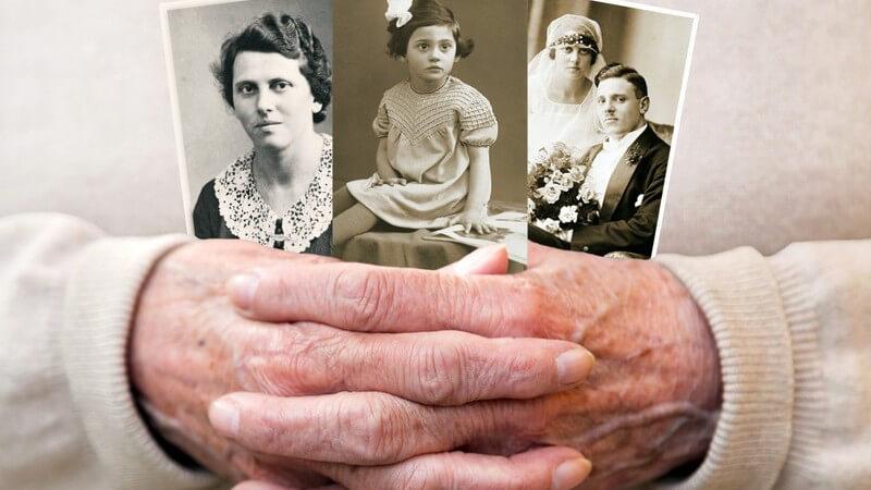 Gefaltete Seniorenhände halten drei alte schwarz-weiße Familienfotos