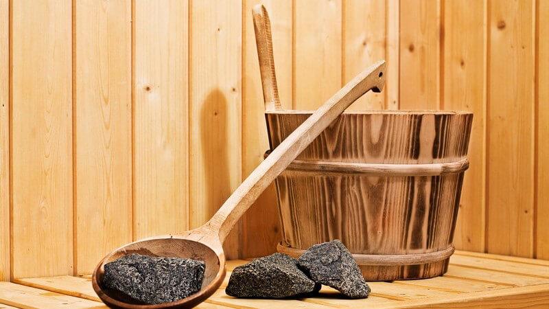 Saunaaufguss: Lavasteine, Eimer und Kelle auf Bank einer Sauna
