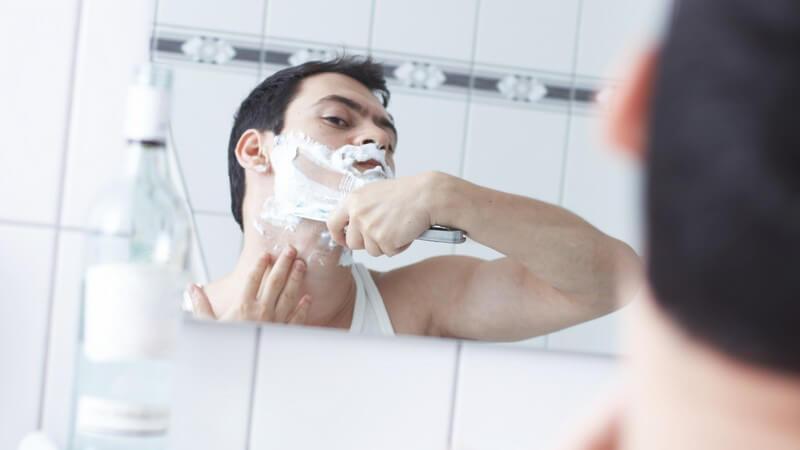 Blick durch Spiegel: Dunkelhaariger Mann rasiert sich den Bart mit Rasiermesser (Nassrasur)