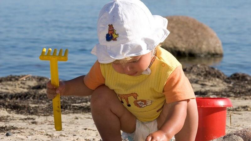 Kleinkind mit Windel und Hut hockt mit Schaufel neben Eimer am Strand