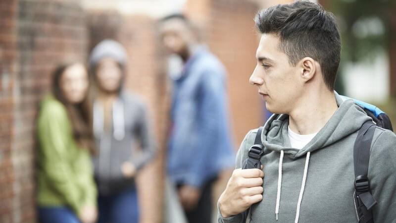 Jugendlicher mit Rucksack auf dem Schulweg, drei Jugendliche in der Nähe scheinen über ihn zu lästern
