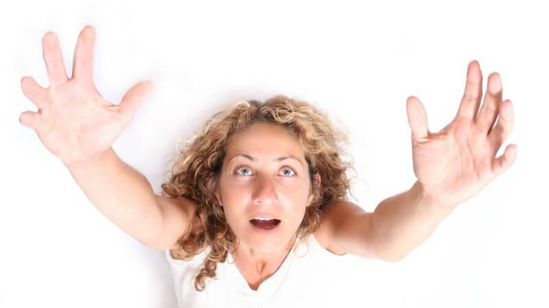 Ansicht von oben: Frau mit ausgebreiteten Armen schaut mit offenem Mund nach oben