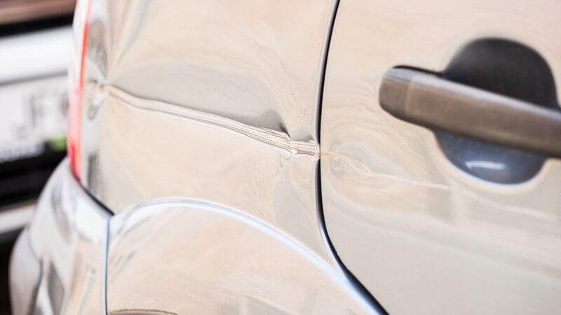 Beule und Kratzer an einem hellen Auto (hinten rechts)