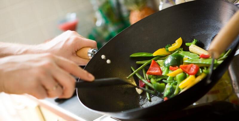 Gemüse wird in Wok zubereitet