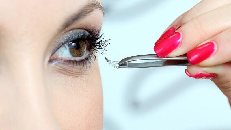 Junge Frau befestigt mit Pinzette künstliche Wimpern