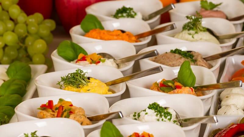 Catering: Buffetplatte mit vielen kleine Schälchen mit Dips, garniert mit Basilikum
