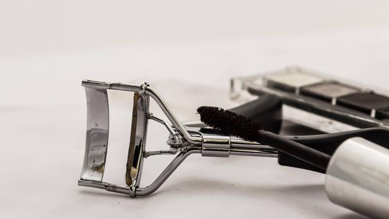 Silberne Wimpernzange und schwarzer Mascara