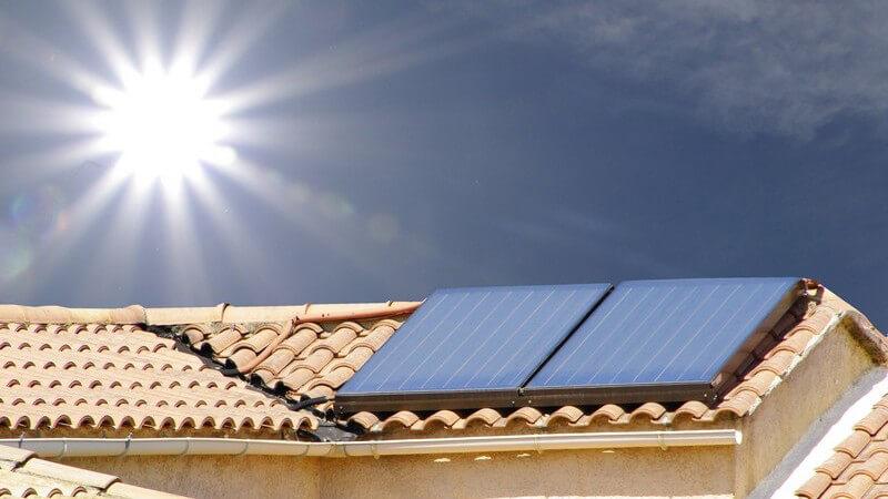 Dach mit Solarzellen, darüber strahlt die Sonne