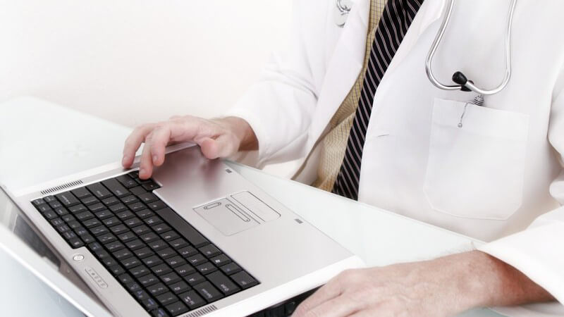 Arzt sitzt am Notebook, Computer