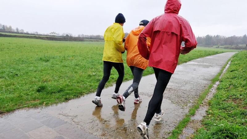Rückansicht drei Sportler beim Joggen im Regen mit Regenjacken