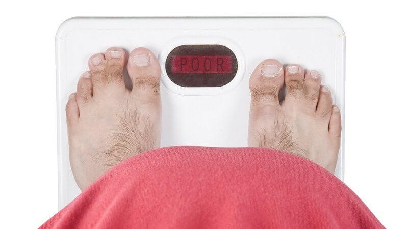 Ansicht von oben: Mann mit dickem Bauch auf Waage