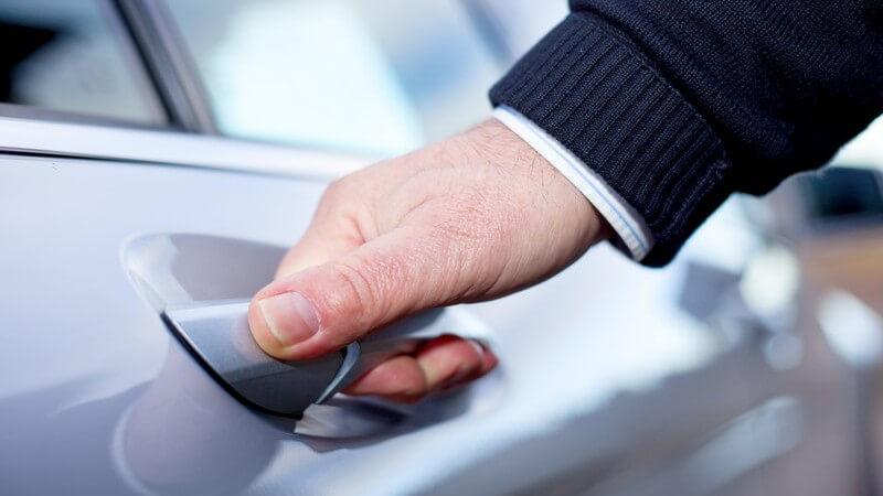 Hand eines Mannes am Türgriff eines grauen Autos