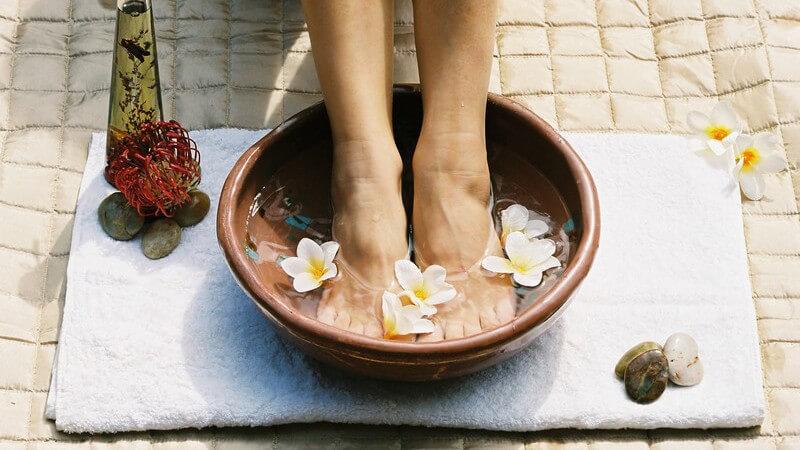 Fußbad in brauner Schüssel auf weißem Handtuch