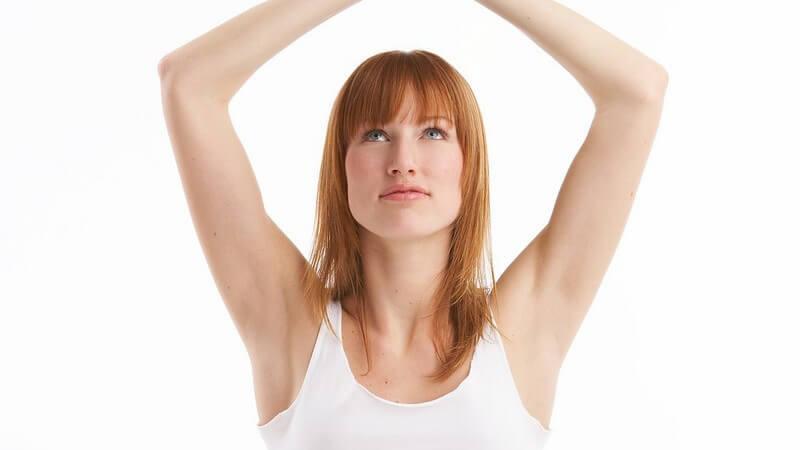 Rothaarige Frau in weißem Oberteil beim Yoga, die Hände über dem Kopf zugespitzt