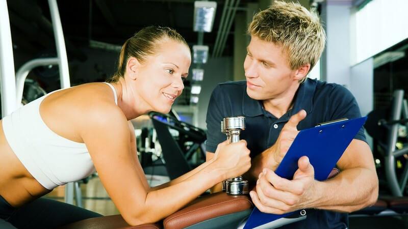 Junge Frau im Fitnesscenter bespricht sich mit ihrem Fitnesstrainer