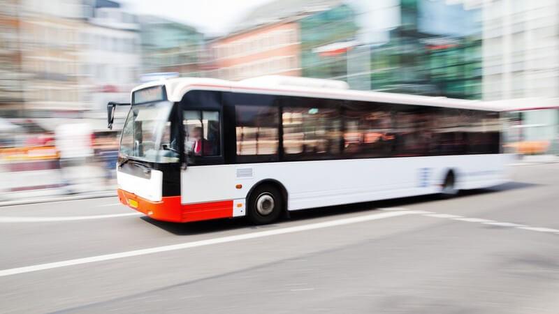 Fahrender Linienbus auf der Straße, im Hintergrund verschwommene Stadt