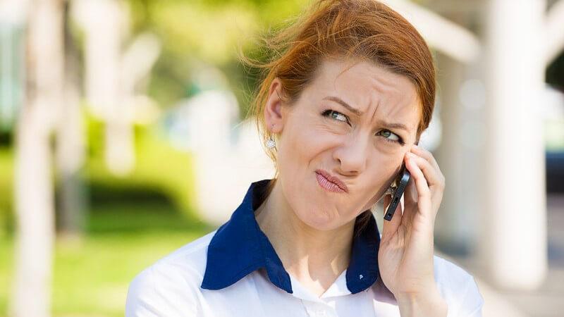 Frau steht draußen und telefoniert mit ihrem Handy, hat einen skeptischen Blick