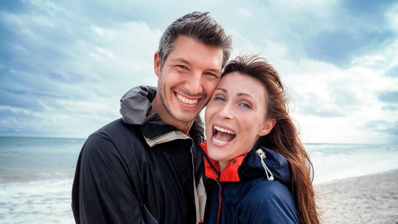 Paar mittleren Alters steht in Regenjacken am windigen Meer und lacht