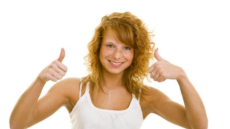 Frau mit roten Locken lacht in Kamera und hält beide Daumen hoch