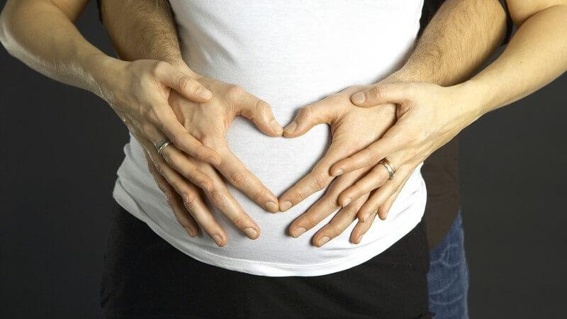 Bauch einer Schwangeren, von hinten von Männerhänden gehalten, die Herz formen